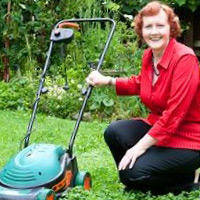 Woman smiling with lawnmower